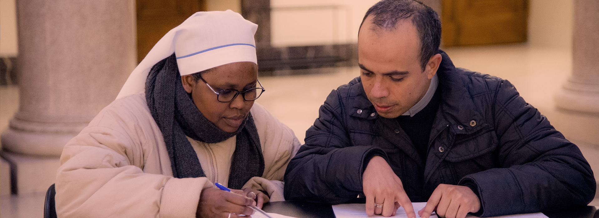 A Nun studying with a seminarian